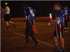 Football player wearing a blue jersey puts on flag football belt