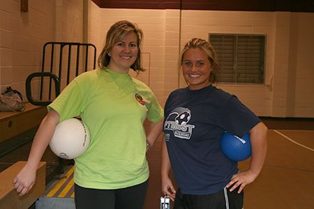 Two women holding volleyballs pose together